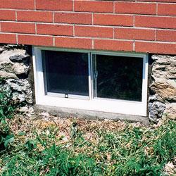 Vue extérieure d'un système de fenêtre de sous-sol en vinyle